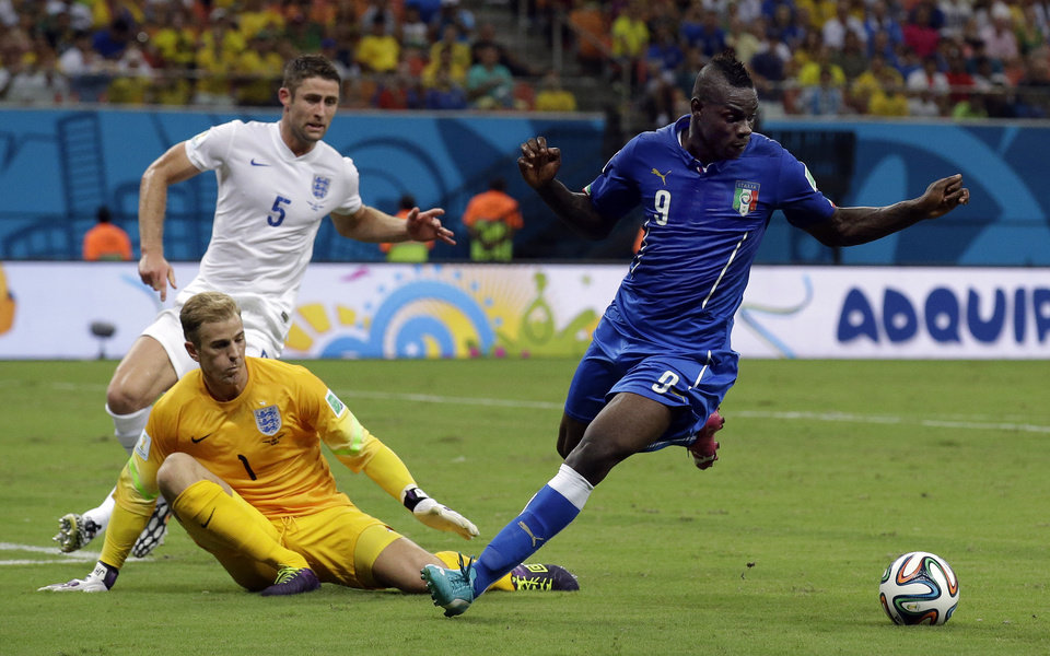 Photo - Italy's Mario Balotelli, right, is closed down by England's goalkeeper Joe Hart and  Gary Cahill, rear, during the group D World Cup soccer match between England and Italy at the Arena da Amazonia in Manaus, Brazil, Saturday, June 14, 2014.  (AP Photo/Matt Dunham)