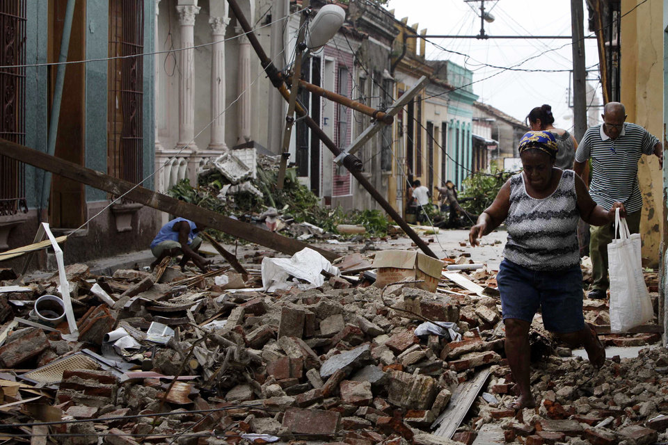 Photo -   Residents walk through the rubble from homes that were damaged by Hurricane Sandy in Santiago de Cuba, Cuba, Friday Oct. 26, 2012. Sandy was a Category 2 hurricane when it wreaked havoc in Cuba on Thursday, killing 11 people in eastern Santiago and Guantanamo provinces as its winds and rain destroyed thousands of houses and ripped off roofs. (AP Photo/Franklin Reyes)
