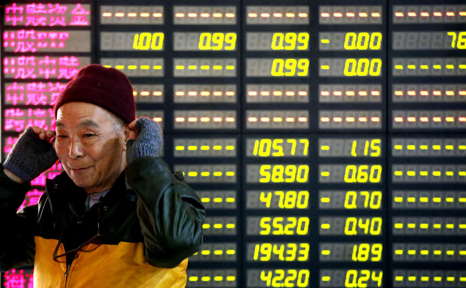 An investor smiles in front of the stock price monitor at a private securities company Tuesday, Nov. 27, 2012 in Shanghai, China. Asian stock markets rose Tuesday after talks over Greece's financial crisis ended with an agreement on how to reduce its debt load, paving the way for the cash-strapped country to receive the next installment of a bailout loan. (AP Photo)
