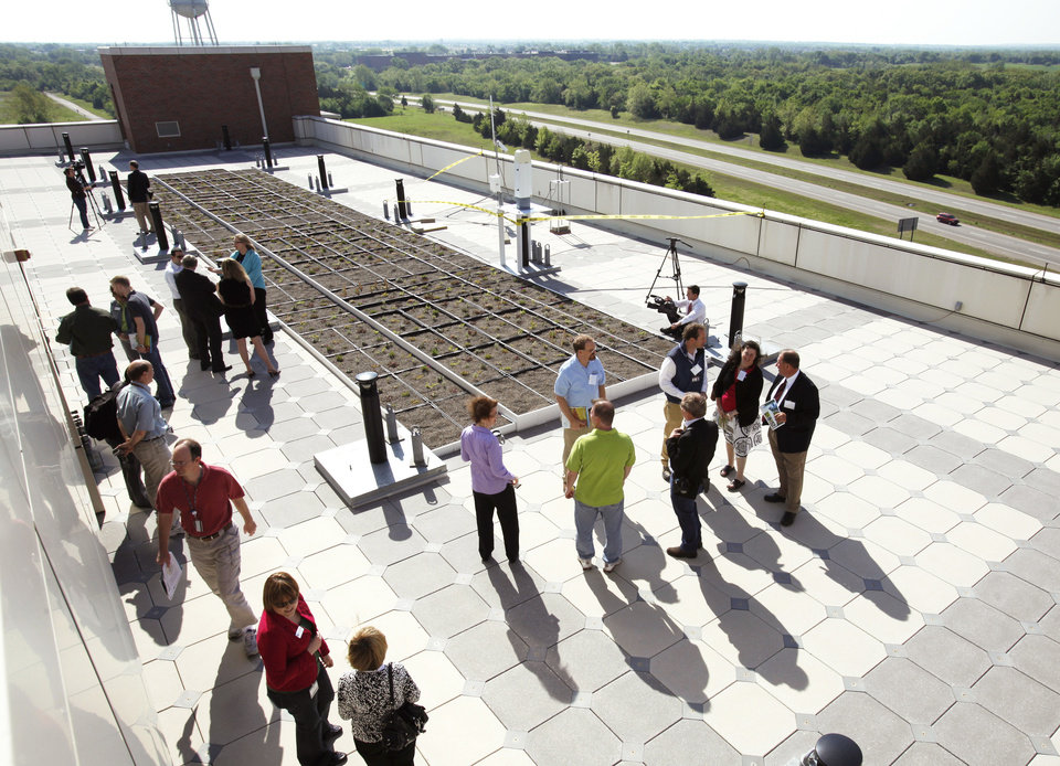 Photo - Visitors attend an open house Thursday for the vegetative roof system atop the National Weather Center at the University of Oklahoma campus in Norman. The green roof is the first of its kind at a university.  Photo by Steve Sisney, The Oklahoman