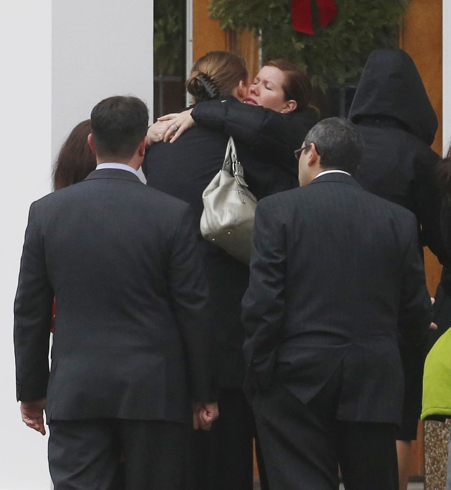 Photo - Mourners embrace outside of St. Rose of Lima Roman Catholic Church during funeral services for James Mattioli, Tuesday, Dec. 18, 2012, in Newtown, Conn. Mattioli, 6, was killed when Adam Lanza walked into Sandy Hook Elementary School in Newtown, Conn., Dec. 14,  and opened fire, killing 26 people, including 20 children, before killing himself. (AP Photo/Julio Cortez)