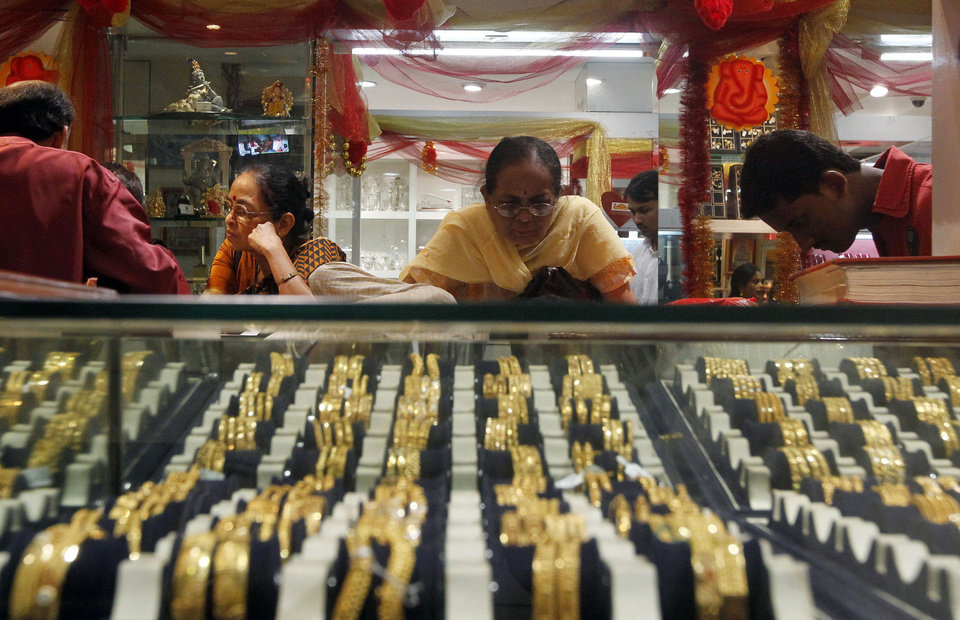 Photo - FILE - In this Thursday, Feb. 14, 2013 photo, an Indian woman looks at a display of gold jewelry at a shop in Mumbai, India.  As of Monday, April 15, 2013, gold has  plunged more than 10 percent the last two days, suggesting that a decade-long surge in the metal is over. Signs that the U.S. economy is healthier are diminishing gold's appeal as an safe place to invest money. Gold peaked at $1,900 in August 2011 and is now at $1,390. (AP Photo/Rajanish Kakade) ORG XMIT: NYBZ109