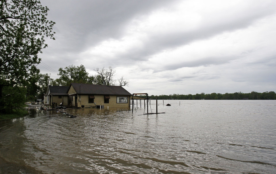 Photo - A home is surrounded by debris and floodwaters in Utica, Ind., Wednesday, April 27, 2011. (AP Photo/Darron Cummings)