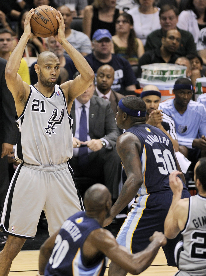 Photo - San Antonio Spurs' Tim Duncan, left, looks to pass around Memphis Grizzlies' Zach Randolph (50) during the second half of Game 1 of the Western Conference final NBA basketball playoff series on Sunday, May 19, 2013, in San Antonio. San Antonio won 105-83. (AP Photo/Darren Abate)