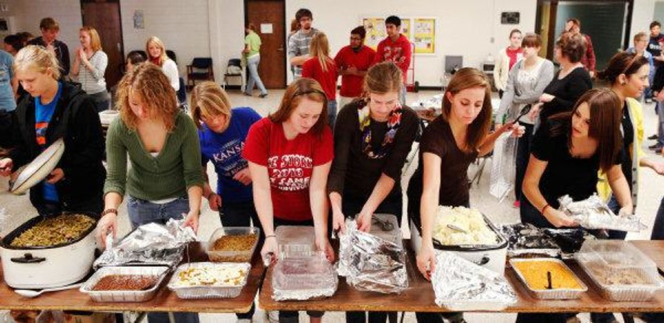 Students remove covers from dishes as food is ready to be served at a holiday meal prepared by Southern Nazarene University student for the Putnam City West High School community. PHOTO BY JIM BECKEL, THE OKLAHOMAN <strong>JIM BECKEL - THE OKLAHOMAN</strong>