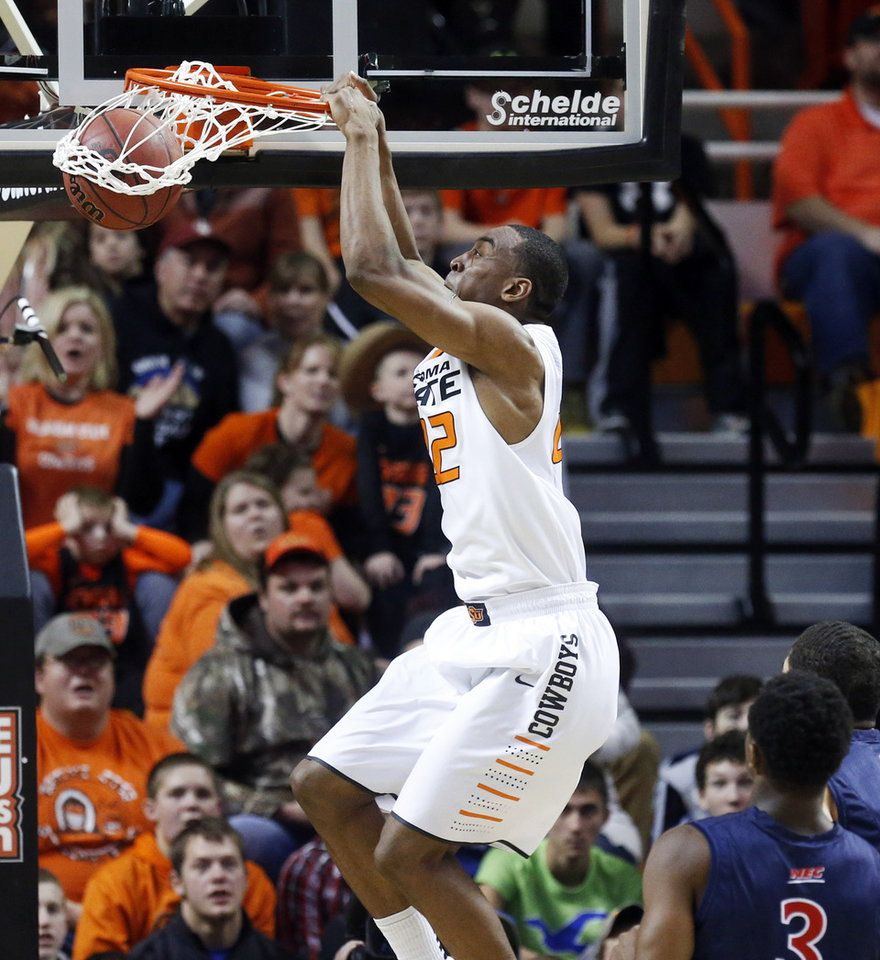 Oklahoma State wing Markel Brown dunks in front of Robert Morris guard Kavon Stewart (3) in the first half of an NCAA college basketball game in Stillwater, Okla., Monday, Dec. 30, 2013. (AP Photo/Sue Ogrocki)