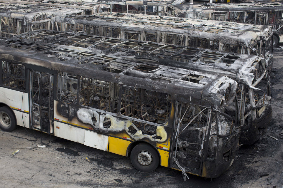 Photo - Passenger buses that were torched a day earlier are parked at a depot in Sao Paulo, Brazil, Wednesday, July 9, 2014. Brazilians woke up Wednesday to dreadful headlines describing the shame and humiliation of their soccer team's historic defeat of 7-1 to Germany in the World Cup's semifinal. There were also reports of violence breaking out right after the game with at least 20 passenger buses being torched in the country's biggest city. (AP Photo/Dario Lopez-Mills)