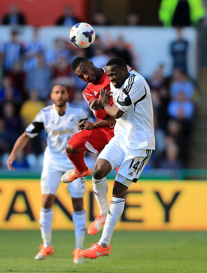 Photo - West Bromwich Albion's Stephane Sessegnon, left, and Swansea City's Roland Lamah battle for the ball during their English Premier League soccer match at the Liberty Stadium, Swansea, Wales, Saturday, March 15, 2014. (AP Photo/Nick Potts, PA Wire)    UNITED KINGDOM OUT   -   NO SALES   -  NO ARCHIVES