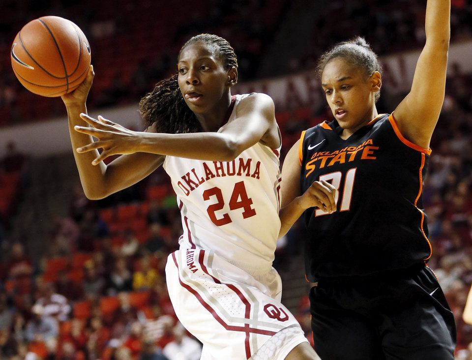 Photo - Oklahoma's Sharane Campbell (24) passes the ball away from Oklahoma State's Kendra Suttles (31) in the second half during a women's Bedlam college basketball game between the Oklahoma State University Cowgirls (OSU) and the University of Oklahoma Sooners (OU) at Lloyd Noble Center in Norman, Okla., Saturday, Feb. 1, 2014. OU won, 81-74. Photo by Nate Billings, The Oklahoman
