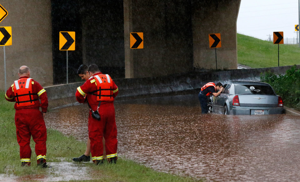 Photo - A firefighter looks into the window of a partially submerged car, checking to see if anyone is inside. This is on the northbound ramp to I-235 from NW 23 Street. Brief periods of heavy rain caused road flooding and created hazardous driving conditions around 7 pm Saturday, May 23, 2015.  Oklahoma City police used their vehicles to barricade all directions of traffic at NW 23 and Broadway, preventing vehicles from driving into high and rushing water. Photo by Jim Beckel, The Oklahoman.