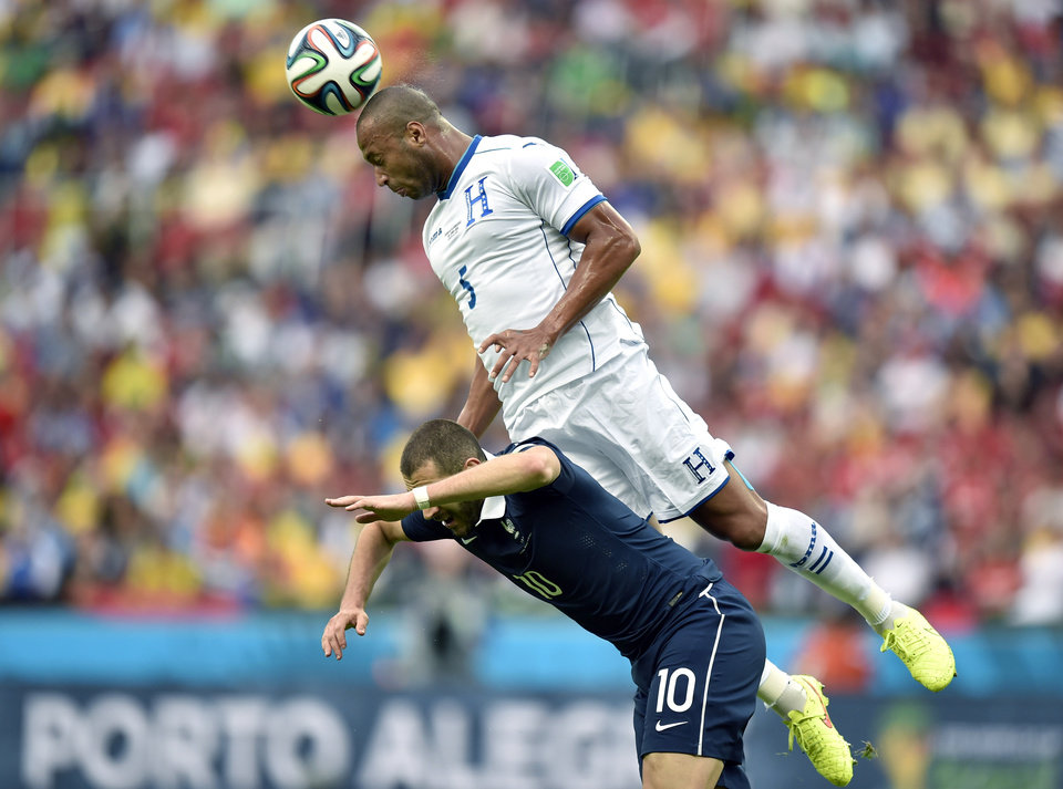 Photo - Honduras' Victor Bernardez leaps over France's Karim Benzema to head the ball during the group E World Cup soccer match between France and Honduras at the Estadio Beira-Rio in Porto Alegre, Brazil, Sunday, June 15, 2014.  (AP Photo/Martin Meissner)