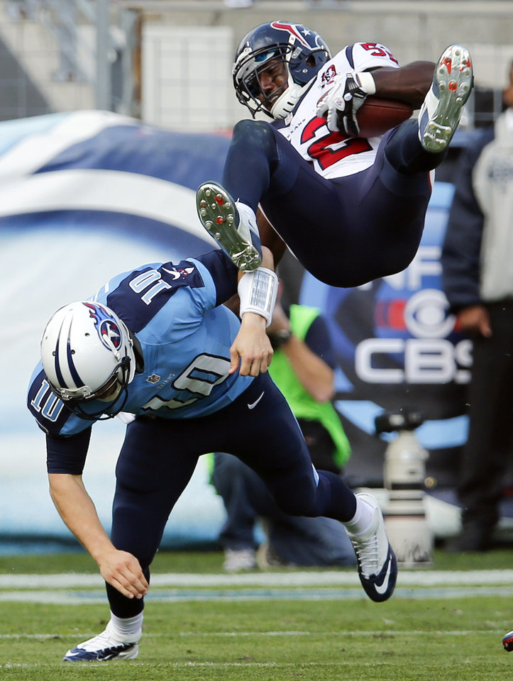 Tennessee Titans quarterback Jake Locker (10) tackles Houston Texans inside linebacker Tim Dobbins (52) after Dobbins intercepted a pass by Locker in the second quarter of an NFL football game on Sunday, Dec. 2, 2012, in Nashville, Tenn. (AP Photo/Joe Howell)