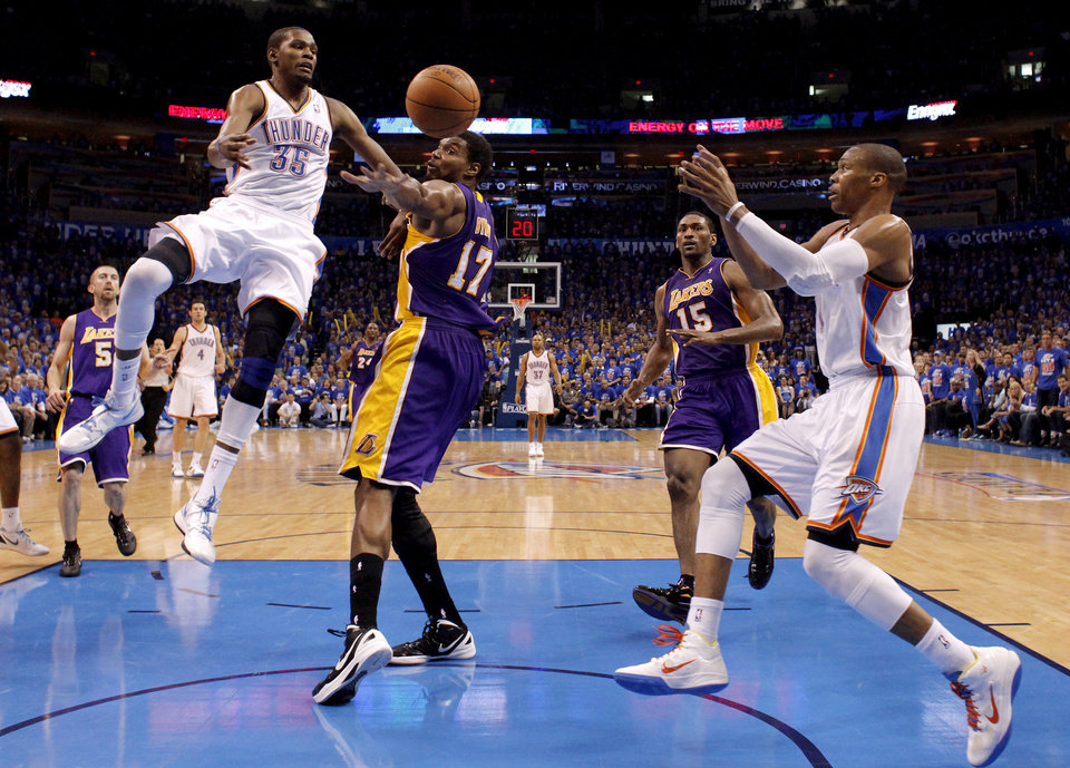 Oklahoma City's Kevin Durant (35) passes the ball past Los Angeles' Andrew Bynum (17) and Metta World Peace (15) to Russell Westbrook (0) during Game 5 in the second round of the NBA playoffs between the Oklahoma City Thunder and the L.A. Lakers at Chesapeake Energy Arena in Oklahoma City, Monday, May 21, 2012. Photo by Bryan Terry, The Oklahoman