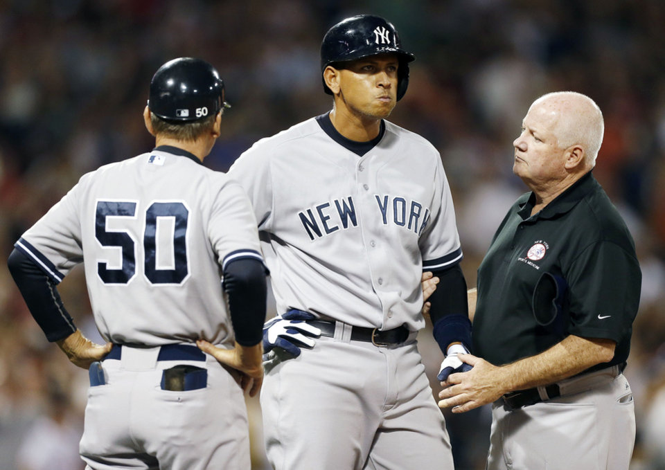 The Yankees� Alex Rodriguez, center, is tended to by a trainer at first base after being hit by a pitch in the second inning Sunday. Rodriguez got hit by a fastball from Boston starter Ryan Dempster. AP Photo