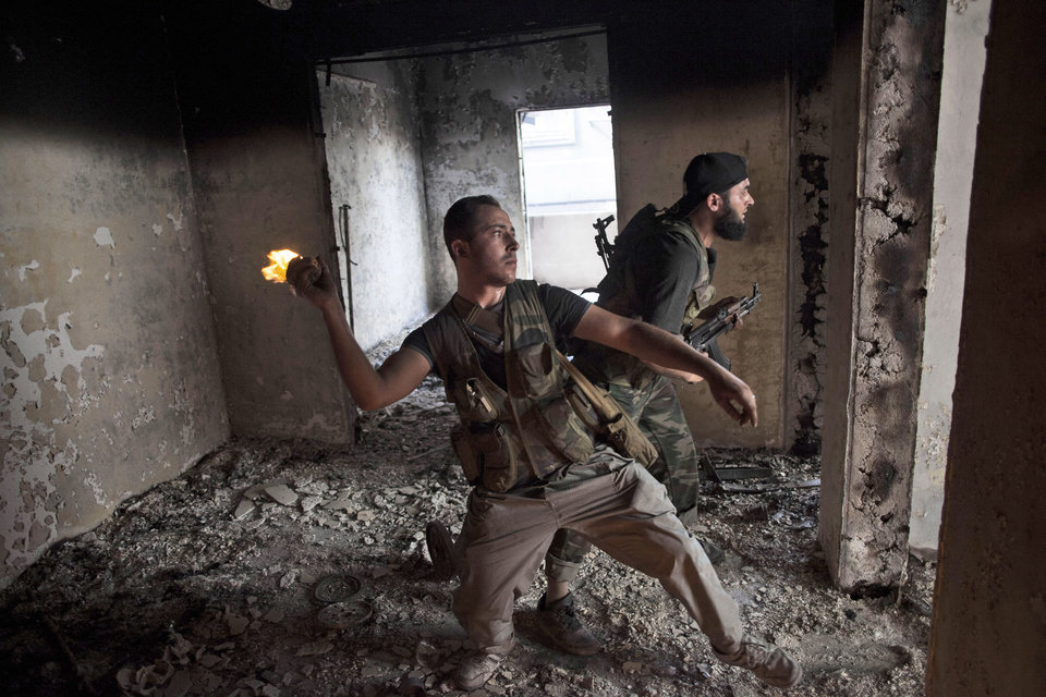 Photo -   Free Syrian Army soldier throws a petrol bomb against Syrian Army positions in Saif Al Dawle district in Aleppo, Syria, Wednesday, Oct. 3, 2012. Three suicide bombers detonated cars packed with explosives in a government-controlled area of the battleground Syrian city of Aleppo on Wednesday, killing at least 34 people, leveling buildings and trapping survivors under the rubble, state TV said. More than 120 people were injured, the government said. (AP Photo / Manu Brabo)