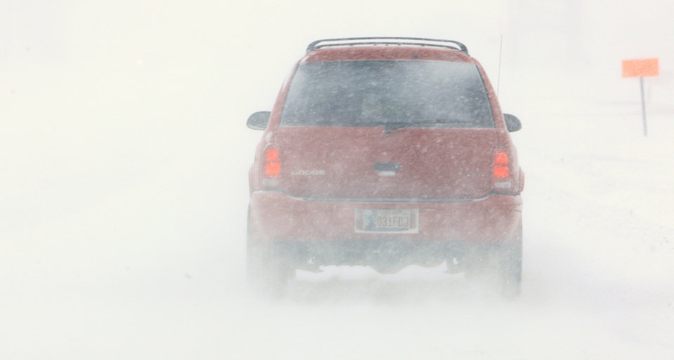 Photo - A car disappears during whiteout conditions while traveling on the NW Expressway in Oklahoma City Tuesday, Feb. 1, 2011.   Photo by Paul B. Southerland, The Oklahoman