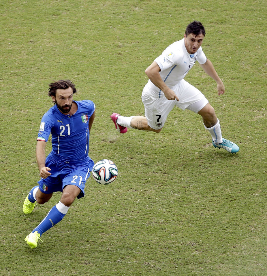Photo - Italy's Andrea Pirlo (21) is challenged by Uruguay's Cristian Rodriguez (7) during the group D World Cup soccer match between Italy and Uruguay at the Arena das Dunas in Natal, Brazil, Tuesday, June 24, 2014. (AP Photo/Hassan Ammar)