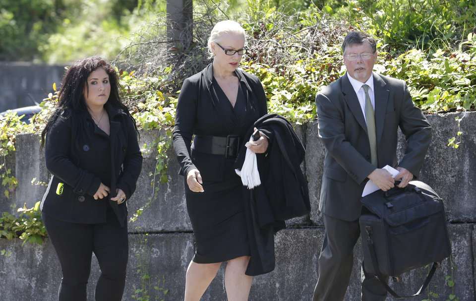 Photo - Jean Kasem, center, the wife of ailing radio personality Casey Kasem, walks with her daughter Liberty Kasem, left, and her attorney Steve Olsen, right, following a hearing in Kitsap County Superior Court, Friday, May 30, 2014 in Port Orchard, Wash. Jean Kasem was in court as part of an ongoing dispute with a stepdaughter who has been given authority to determine whether her father is receiving adequate medical care. Kasem and his wife have been staying with family friends in Washington state. (AP Photo/Ted S. Warren)