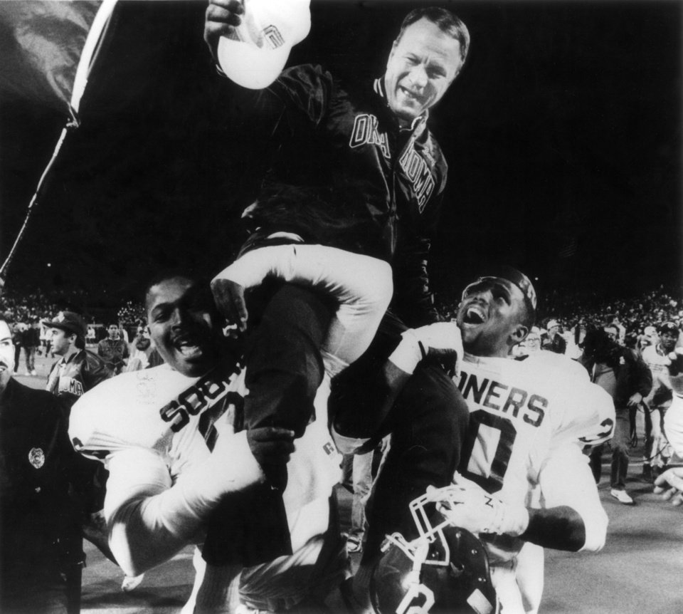 Photo - OU head college football coach Barry Switzer is carried off the field on the shoulders of Billy Dykes, left, and Chris Wilson after defeating OSU on Saturday, Nov 5, 1988 in the Bedlam college football game.  Staff photo by David McDaniel