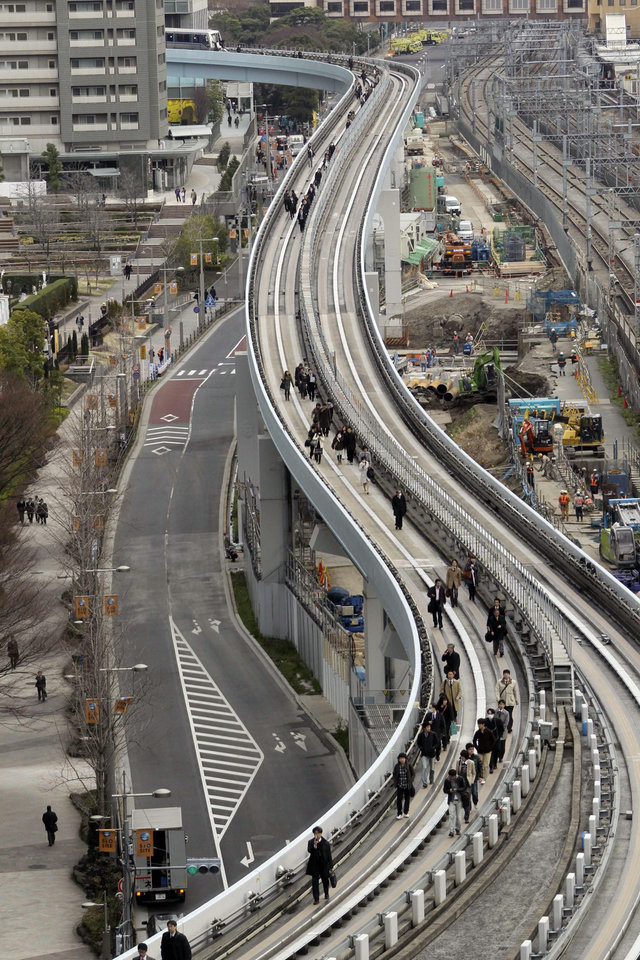 Photo - Yurikamome train passengers walk on the elevated track towards Shiodome Station in Tokyo near Tokyo Bay Friday, March 11, 2011, shortly after a  7.9-magnitude earthquake has struck off Japan's northeastern coast. (AP Photo/Koji Sasahara) ORG XMIT: TOK105