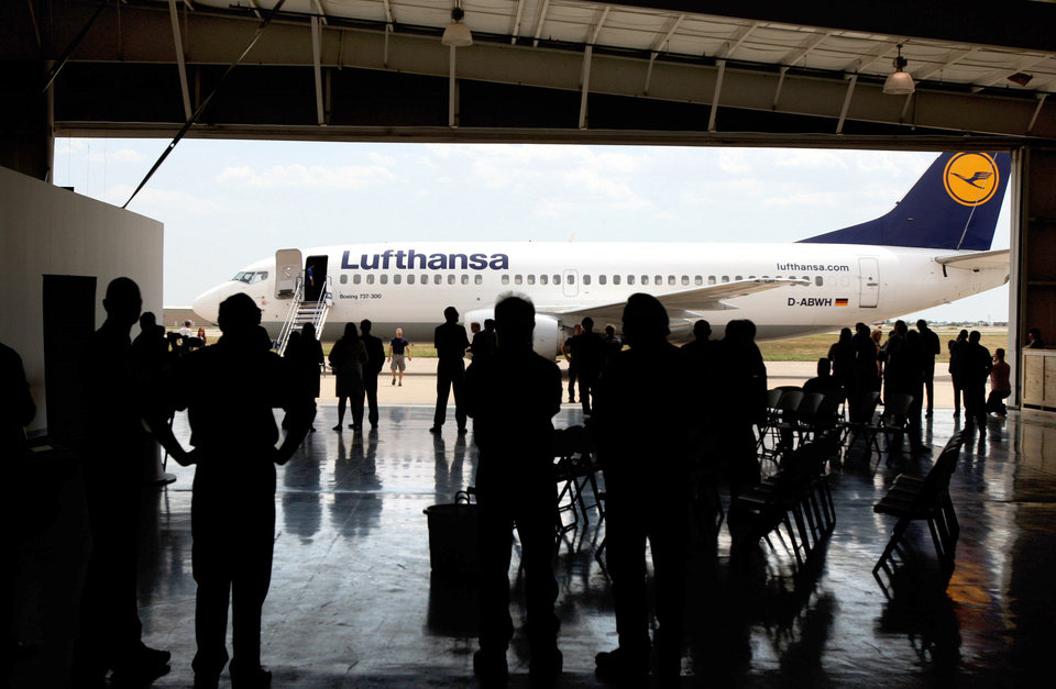 Photo - Employees and media view a Lufthansa airliner Aug. 1 following a news conference where officials announced a facilities and work force expansion for the company in Tulsa. Photo by Cory Young, Tulsa World.  Cory Young - AP