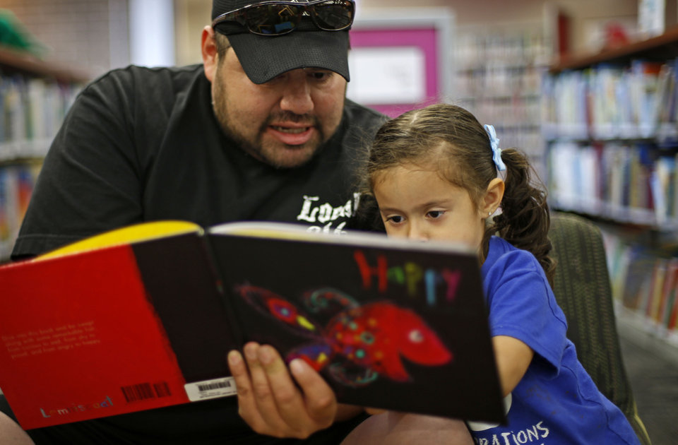 German Contreras reads to his daughter Natali, 3, during the grand reopening of Southern Oaks Library in Oklahoma City. Photos by Bryan Terry, The Oklahoman