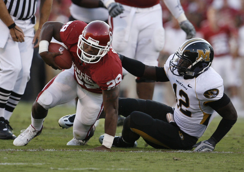 Photo - Chris Brown rolls over Missouri defender Sean Weatherspoon and head for the goal during the first half of the college football game between the University of Oklahoma Sooners (OU) and the University of Missouri Tigers (MU) at the Gaylord Family Oklahoma Memorial Stadium on Saturday, Oct. 13, 2007, in Norman, Okla.  The play was reviewed and he was ruled down.  By STEVE SISNEY, The Oklahoman