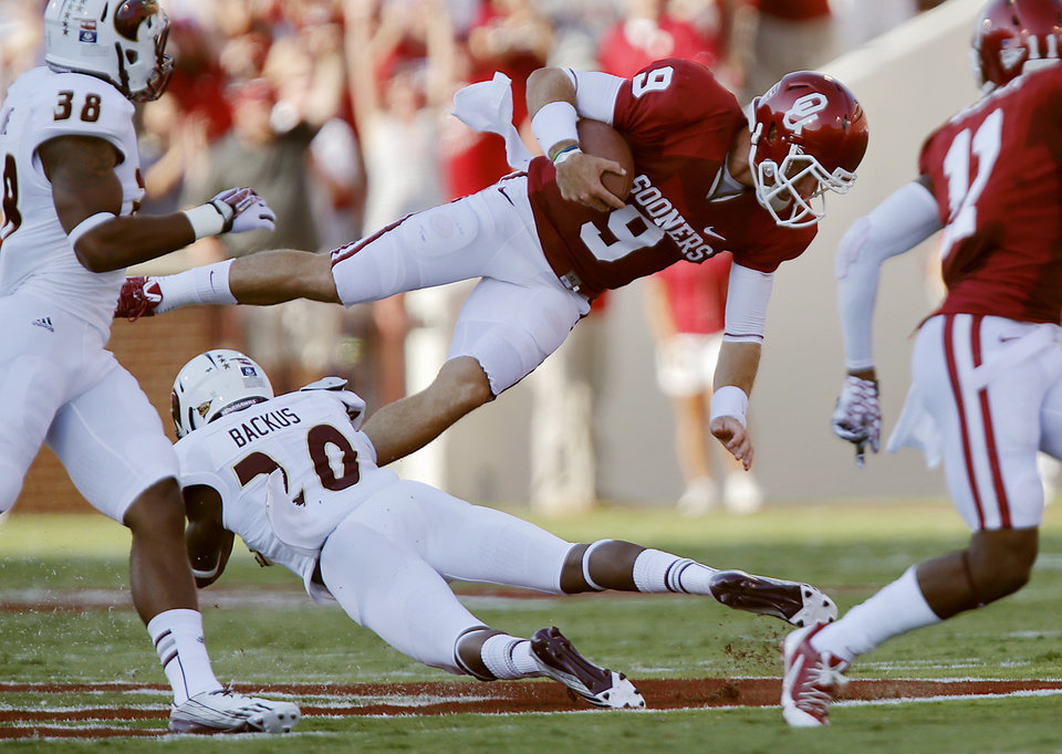 Oklahoma's Trevor Knight (9) is tripped up by Louisiana Monroe's Justin Backus (20) during the college football game between the University of Oklahoma Sooners (OU) and the University of Louisiana Monroe Warhawks (ULM) at the Gaylord Family Memorial Stadium on Saturday, Aug. 31, 2013 in Norman, Okla.  Photo by Chris Landsberger, The Oklahoman