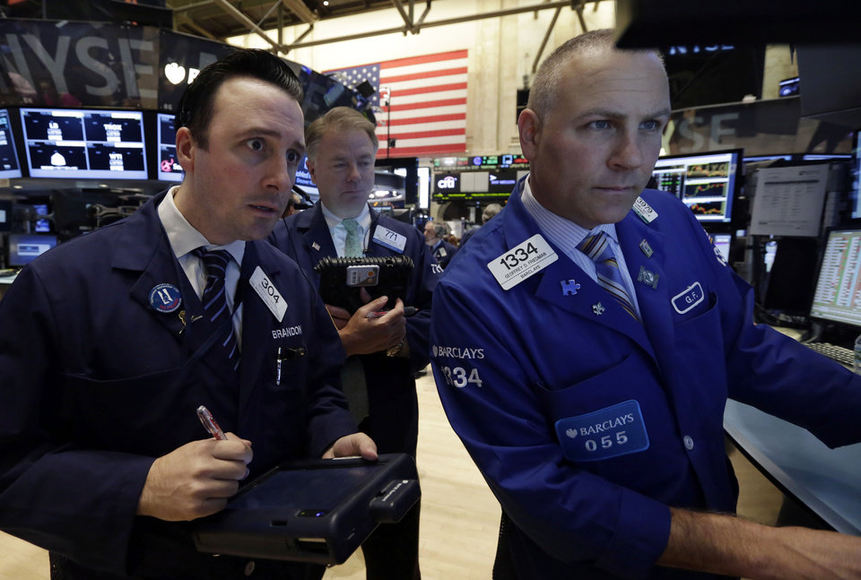 Photo - Specialist Geoffrey Friedman, right, works with traders on the floor of the New York Stock Exchange Thursday, Aug. 7, 2014. U.S. stocks are opening slightly higher after Europe's main two central banks decided to keep interest rates on hold. (AP Photo/Richard Drew)