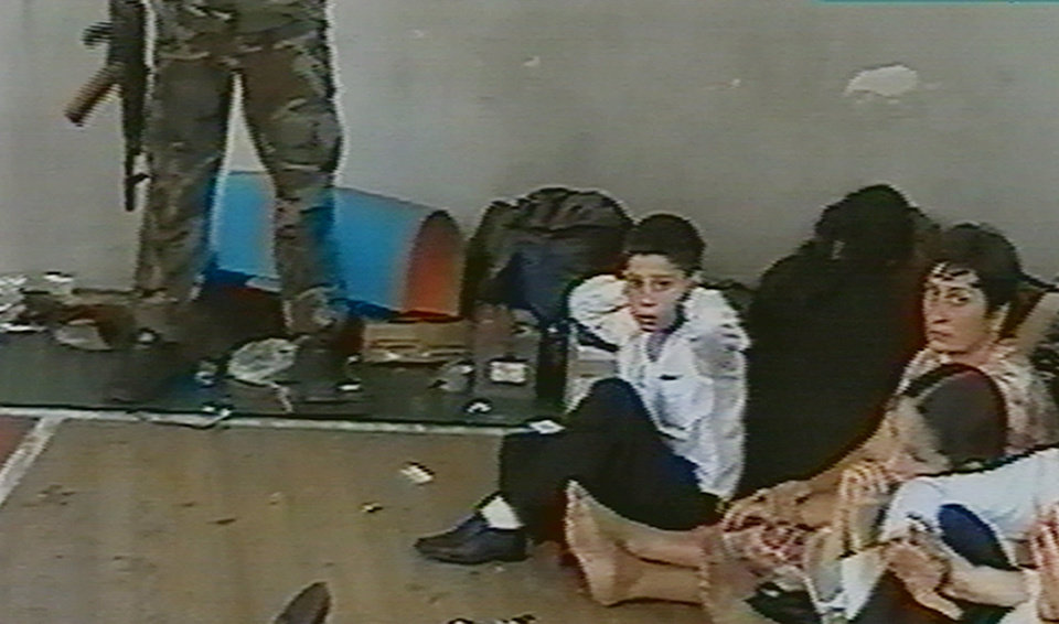 Photo - FILE - Hostages sit on a floor in a gym as a hostage-taker stands with his left foot on a book apparently with a device connected to a chain of explosives in the school in Beslan, Russia taken  in this undated image from television during the early part of the siege which began on  Sept. 1, 2004 and ended with over 300 people dead. Two suspects in the Boston Marathon bombing have been identified to The Associated Press as coming from a Russian region near Chechnya  In the past, insurgents from Chechnya and neighboring restive provinces in the Caucasus have been involved in terror attacks in Moscow and other places in Russia. (AP Photo/NTV-Russian Television Channel, File)