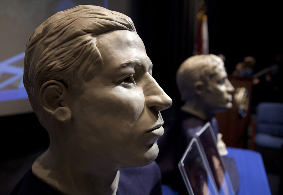 FILE - In this March 6, 2012 file photo, phases of facial reconstruction of the two sailors of the Civil War ironclad USS Monitor, older is at left, are on display in the auditorium of the United States Navy Memorial in Washington. The remains of the two unknown Union sailors recovered from the Civil War ironclad USS Monitor will be interred in Arlington National Cemetery on March 8.  A century and a half after the USS Monitor sank, the interment of remains of two unknown sailors found in the Civil War ironclad�s turret is bringing together nearly 100 people from Maine to California who have a distant familial tie to the 16 Union sailors who died when the ship went down. (AP Photo/Carolyn Kaster, File)