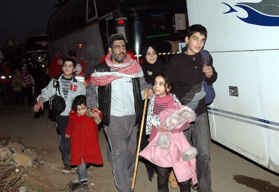 Photo - In this photo taken on Sunday Feb. 9, 2014, and released by the Syrian official news agency SANA, Syrian citizens walk towards a bus to evacuate the battleground city of Homs, Syria. A Syrian Red Crescent official says around 300 more people were evacuated Monday from besieged rebel-held neighborhoods of Syria's third-largest city, Homs. (AP Photo/SANA)