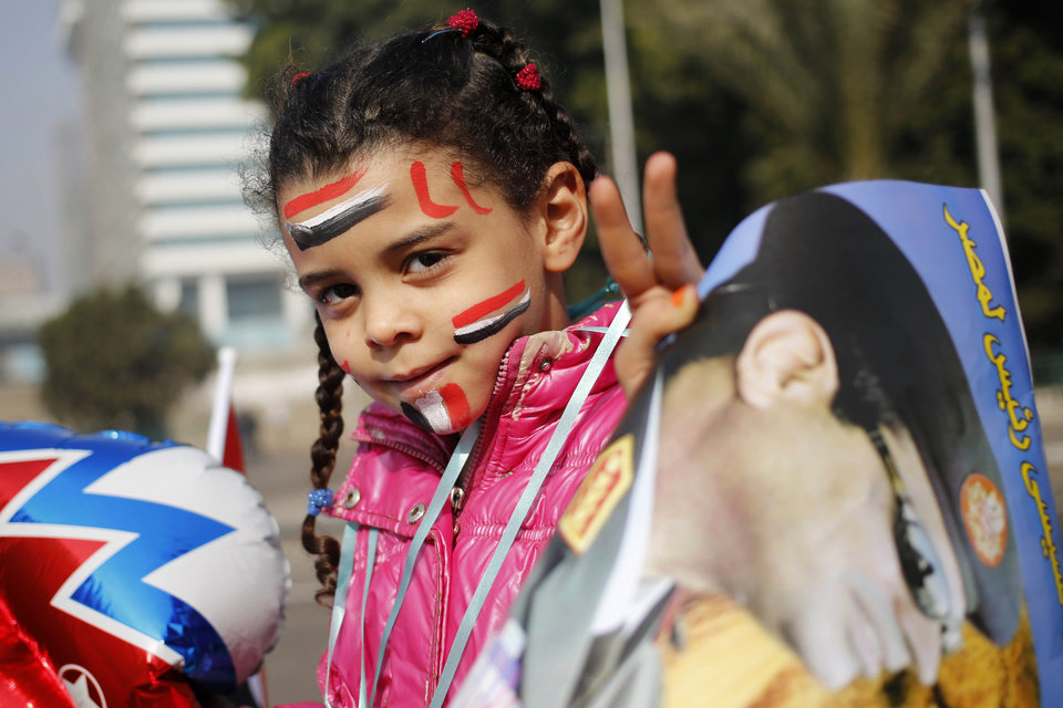 Photo - An Egyptian girl holds a poster of Egypt's Defense Minister, Gen. Abdel-Fattah el-Sissi, in Tahrir Square, the epicenter of the 2011 uprising, in Cairo, Egypt, Saturday, Jan. 25, 2014. Egyptian riot police have fired tear gas to disperse hundreds of supporters of ousted Islamist President Mohammed Morsi protesting as the country marks the third anniversary of the 2011 uprising, as supporters of the military gathered in rival rallies in other parts of the capital, many of them urging military chief el-Sissi, the man who removed Morsi, to run for president.(AP Photo/Hassan Ammar)