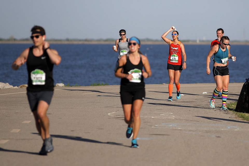 Photo - Jenna Negley pours water over her head as she makes he way around Lake Hefner during the Oklahoma City Memorial Marathon in Oklahoma City, Sunday, April 29, 2018. Photo by Bryan Terry, The Oklahoman