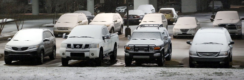 Photo - Cars in this car dealer's lot in Flowood, Miss., show the accumulation of snow early Thursday morning Jan. 17, 2013, in Flowood, Miss. The National Weather Service says central Mississippi could get from 2 to 4 inches of snow from midnight through midmorning Thursday. (AP Photo/Rogelio V. Solis)