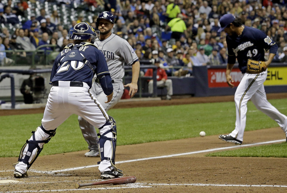 Photo - Milwaukee Brewers starting pitcher Yovani Gallardo (49) can't handle a bunt by San Diego Padres' Ian Kennedy as Yonder Alonso approaches the plate and Jonathan Lucroy before scoring during the fifth inning of a baseball game Tuesday, April 22, 2014, in Milwaukee. (AP Photo/Morry Gash)