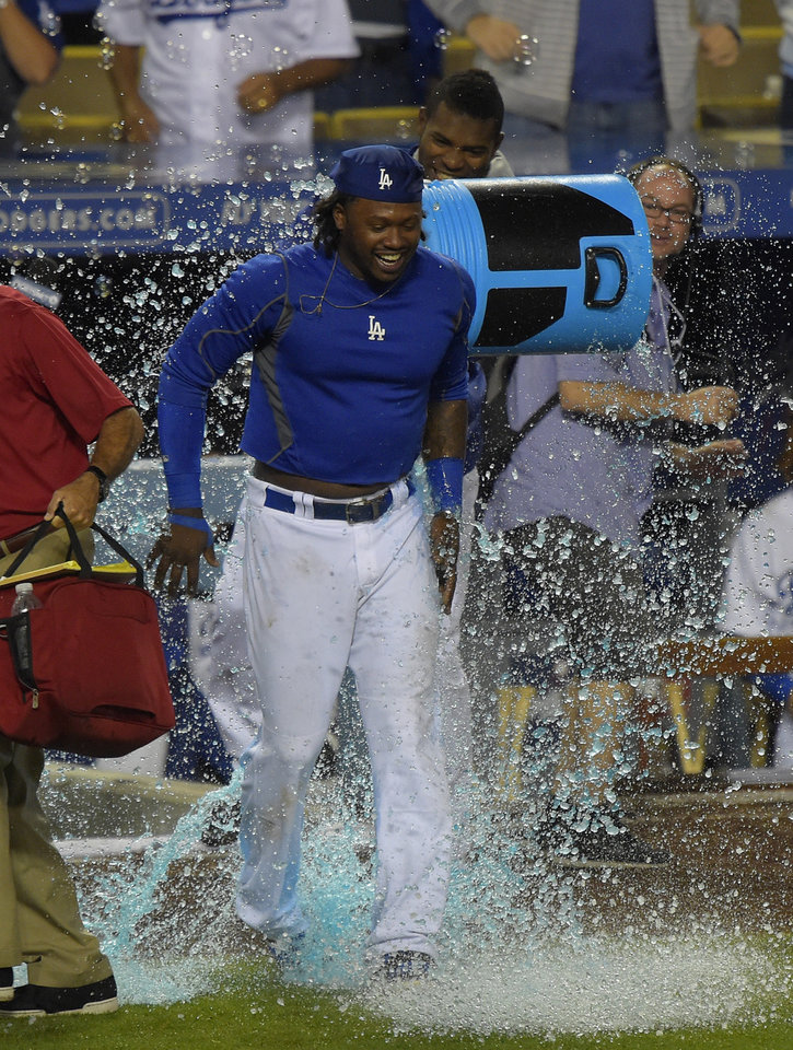 Photo - Los Angeles Dodgers' Hanley Ramirez, left, gets liquid dumped on him by Yasiel Puig after hitting a three-run home run to win the game during the 12th inning of a baseball game against the Chicago Cubs, Saturday, Aug. 2, 2014, in Los Angeles. (AP Photo/Mark J. Terrill)