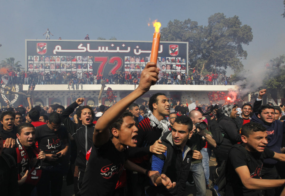 Photo - Egyptian soccer fans of Al-Ahly club celebrate in front of their club in Cairo, Egypt, Saturday, March 9, 2013 An Egyptian court confirmed death sentences against 21 people for their role in a deadly 2012 soccer riot that killed more than 70 people in the city of Port Said. Banner at background showing some pictures of the victims with Arabic that reads,