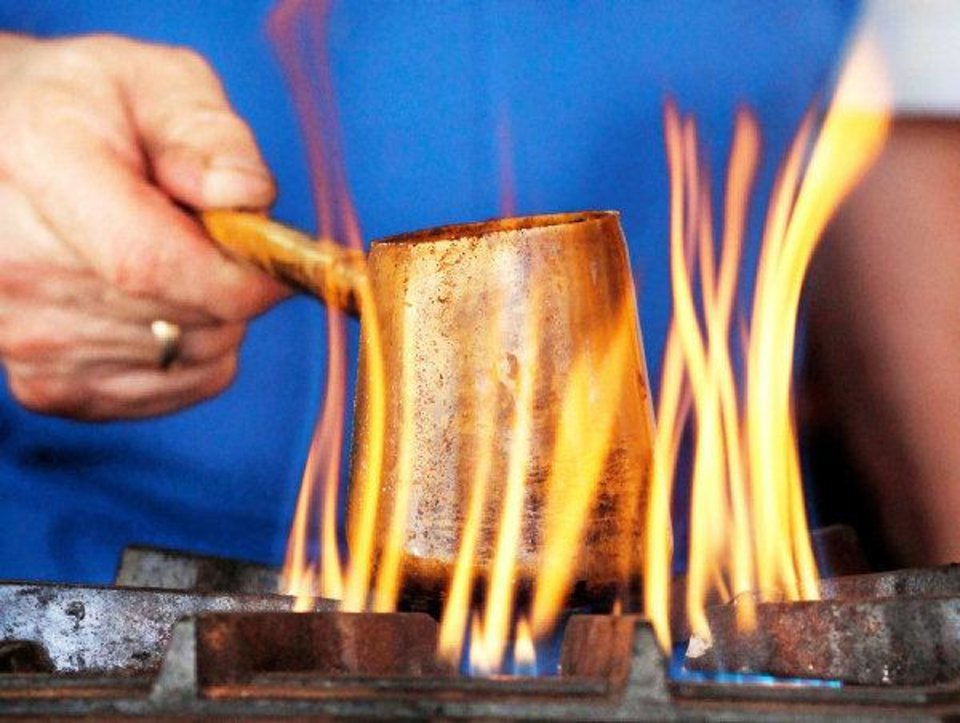 Photo - Gus Gianos prepares a fresh serving of Greek coffee  Friday, Sep. 9, 2011, during the 27th annual Greek Festival at St. George Greek Orthodox Church in far northwest Oklahoma City.  Gianos said Greek coffee is not percolated but each cup of the  beverage is cooked fresh  over a flame and served hot.  He said the sugar is added during the cooking process and he said the taste is stronger than most other coffees.   Gianos has been working at the festival since it began. Photo by Jim Beckel, The Oklahoman  ORG XMIT: KOD