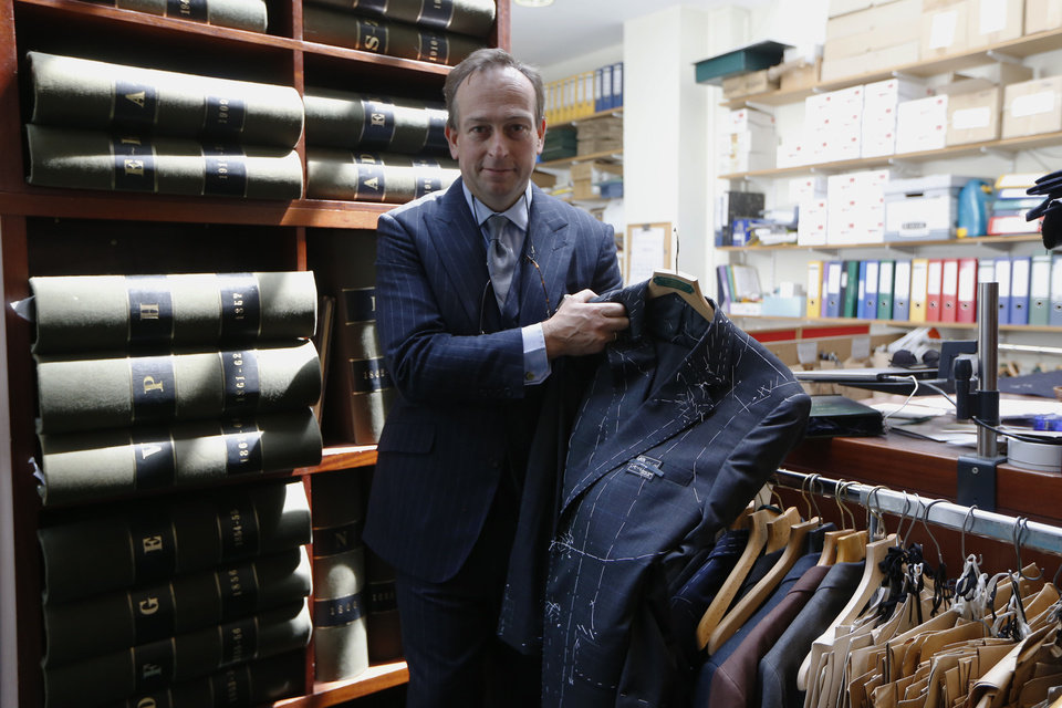 Photo - In this photo taken Friday, June 6, 2014, Simon Cundey, managing director of Henry Poole & Co tailor, the first shop to set up in Savile Row in 1846, displays a suit in its fitting stage as he speaks to Associated Press at his store on Savile Row in London. In the world of women's fashion, London often seems to play second fiddle to other style capitals: It lacks the allure of Paris's haute couture, or the polish of Milan's luxury labels. But it's a whole different story when it comes to dressing men. Steeped in a rich history of tailoring for kings, army generals and the world's wealthiest men, London is now marketed as the home of men's fashion - the original birthplace of the tuxedo jacket, the bowler hat and the three-piece suit, among other classic items. When trendy designers like Alexander McQueen and Burberry kick off the new season's menswear shows in the British capital Sunday, the catwalks will be staged just blocks away from elite tailoring houses that have been perfecting their craft for over a century. Savile Row, a street lined with more than a dozen tailors and a living museum of the English love affair with luxury menswear, has a long-standing tradition closely tied to a history in royal dress, military uniforms and gentry sports like horseback riding and hunting. (AP Photo/Sang Tan)