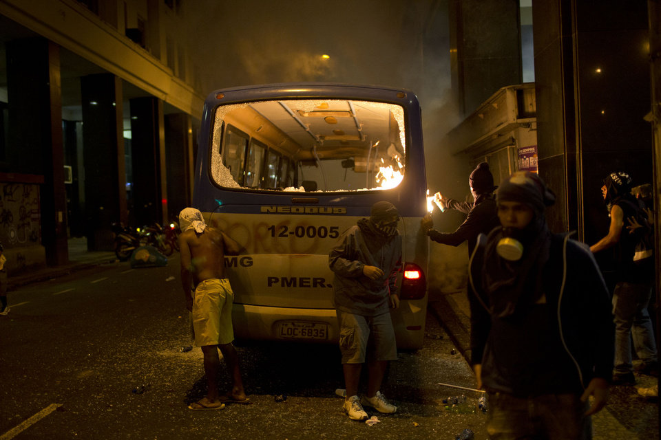 Photo - Masked members of the so-called Black Bloc anarchist group set fire to a police bus after a march of striking teachers marked National Teachers Day, in Rio de Janeiro, Brazil, Tuesday, Oct. 15, 2013. Last week, a largely peaceful rally of teachers turned violent in Rio when small groups of masked protesters started hurling rocks and gasoline bombs and set fire to a passenger bus. Black Bloc anarchists, who earlier joined in the march with teachers, tried to incite the crowd Tuesday but were kept in check by other demonstrators. (AP Photo/Felipe Dana)