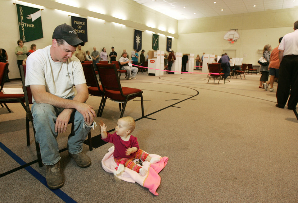 Photo - Ben Huskey plays with his 9 month old daughter Kyla as he waits in line to vote at Woodcrest Baptest Church in Logan County , Okla. November 04, 2008.  BY STEVE GOOCH, THE  OKLAHOMAN.  ORG XMIT: KOD