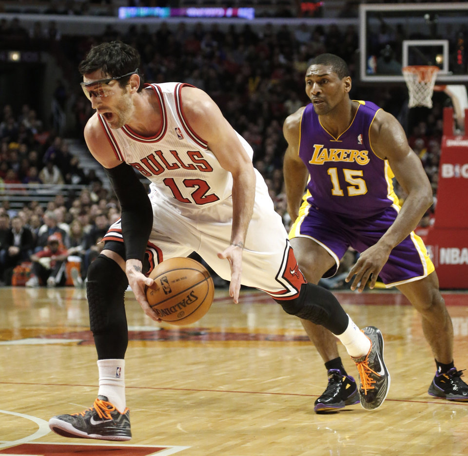 Photo - Chicago Bulls guard Kirk Hinrich (12) drives past Los Angeles Lakers forward Metta World Peace during the second half of an NBA basketball game Monday, Jan. 21, 2013, in Chicago. The Bulls won 95-83. (AP Photo/Charles Rex Arbogast)