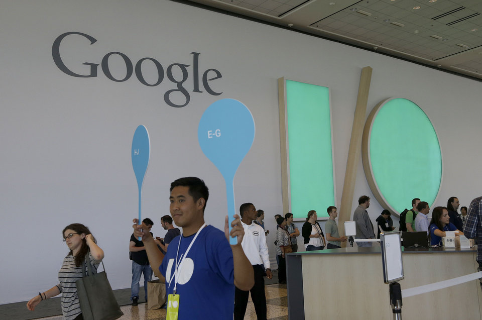 Photo - A Google employee helps direct people as they register for Google I/O 2014 in San Francisco, Tuesday, June 24, 2014. (AP Photo/Jeff Chiu)