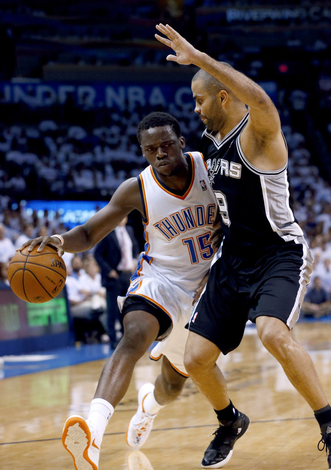 Photo - Oklahoma City Thunder guard Reggie Jackson (15) drives against San Antonio Spurs guard Tony Parker (9) during the first half of Game 6 of the Western Conference finals NBA basketball playoff series in Oklahoma City, Saturday, May 31, 2014. (AP Photo/Sue Ogrocki)