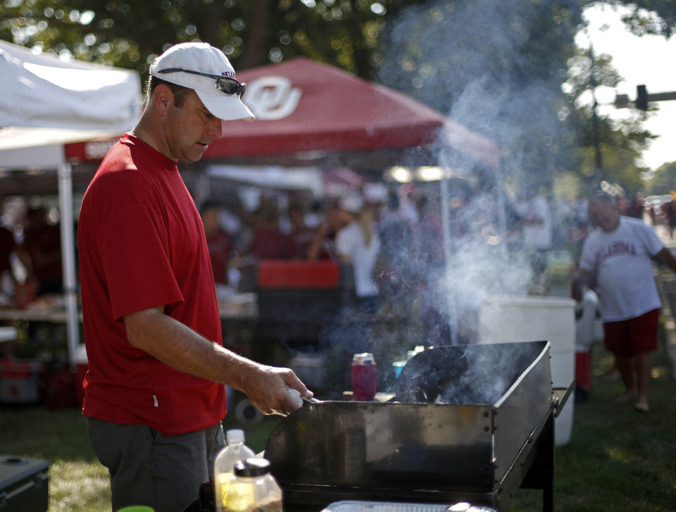 Photo - Jay Edzards of Norman grills food before a college football game between the University of Oklahoma Sooners (OU) and the West Virginia University Mountaineers at Gaylord Family-Oklahoma Memorial Stadium in Norman, Okla., on Saturday, Sept. 7, 2013. Photo by Bryan Terry, The Oklahoman