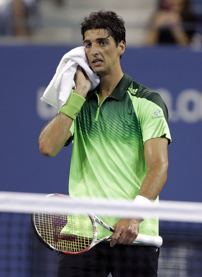 Photo - Thomaz Bellucci, of Brazil, wipes his faces after having his serve broken during a match against Stan Wawrinka, of Switzerland, during the second round of the U.S. Open tennis tournament Wednesday, Aug. 27, 2014, in New York. (AP Photo/Darron Cummings)