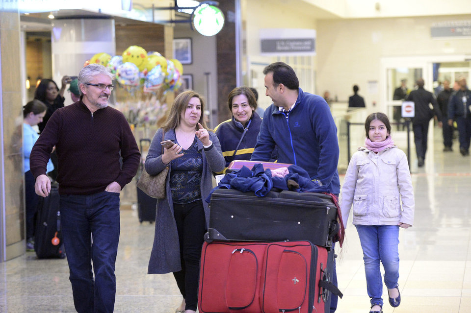 Photo - Mansour Kenereh, second left, walks with family members in the International arrivals lobby at Hartsfield- Jackson Atlanta International Airport, Saturday, Jan. 25, 2017, in Atlanta. The family of 3 were among people detained at the U.S. Customs and Border Protection office following an executive order from President Donald Trump limiting immigration. (Kent D. Johnson/Atlanta Journal-Constitution via AP)
