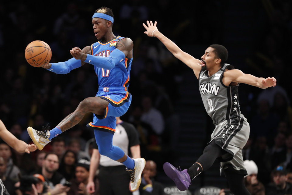 Photo - Oklahoma City Thunder guard Dennis Schroder (17) passes as Brooklyn Nets guard Spencer Dinwiddie (8) defends during the second half of an NBA basketball game, Tuesday, Jan. 7, 2020, in New York. The Thunder defeated the Nets 111-103 in overtime. (AP Photo/Kathy Willens)
