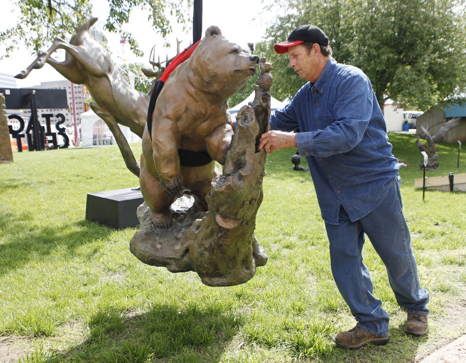 Photo - SET UP / PREPARE / PREPARATION: Gary Guedry guides a bronze sculpture into position at the Festival of the Arts in downtown Oklahoma City, OK, Monday, April 19, 2010. By Paul Hellstern, The Oklahoman ORG XMIT: KOD